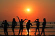 Group Of Friends Having Fun stand on the beach at sunset