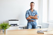 Happy man standing by his desk in office