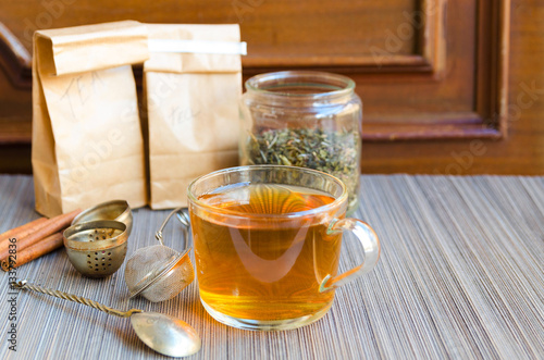 Fotografie, Obraz  Glass cup of hot tea with spoon infuser and tea jar on grey straw background