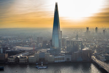 One Of The Tallest Buildings In London - The Shard Tower Rising Above The River Thames And Everything Around. Foggy Skyline Is Painted With Beautiful Orange Sunset.