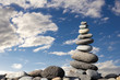 Zen stones on the beach with blue cloudy sky