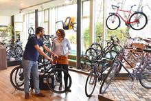 Fahrradgeschäft: Verkäufer Und Kundin Beim Verkaufsgespräch // Bike Shop