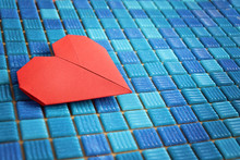 Valentine's Day Paper Origami Red Heart  Placed On Blue Swimming Pool Tile Background
