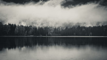 Clouds And Forest Reflected In A Lake.
