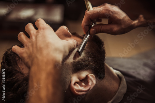 Men barber shaves his beard. Fotobehang
