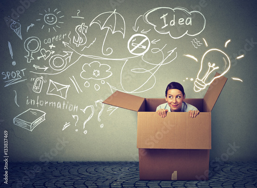 Foto  Think outside box. Young woman coming out of box