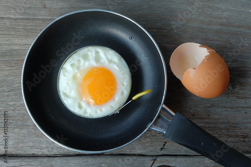 Deurstickers Gebakken Eieren fried egg with pan on wood floor