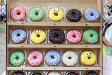 Assorted Tasty Colorful Donuts On Wooden Showcase, Close Up View