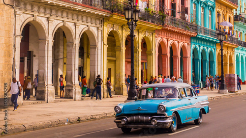 Foto auf Gartenposter Havana A blue oldtimer taxi is driving through Habana Vieja in front of a colorful facade