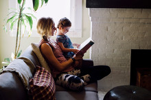 Woman On Sofa With Toddler Daughter Reading Storybook