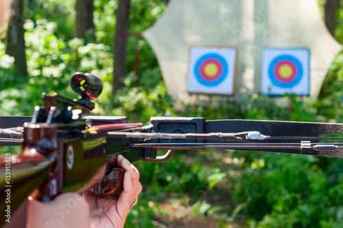 Fényképezés Woman aiming crossbow at target