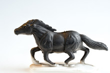 Black Galloping Plastic Toy Horse On A White Background