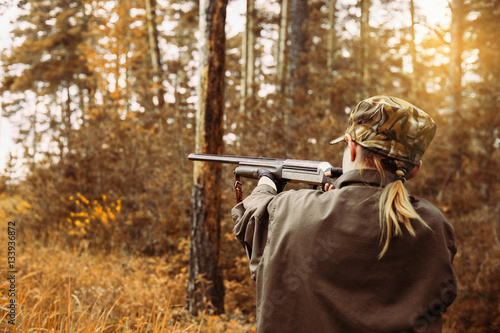 Fotobehang Jacht Autumn hunting season. Woman hunter with a gun.