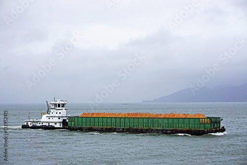 Fotografia  pusher tug and barge going up the Columbia river in Astoria Oregon