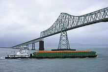 Pusher Tug And Barge Heading Up The Columbia River And Passing Under The Astoria-Megler Bridge