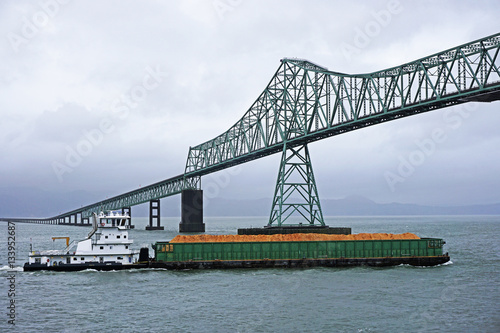 Fotografia  pusher tug and barge heading up the Columbia river and passing under the Astoria