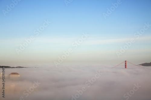 Papiers peints Ciel Majestic view of clouds covering Golden Gate Bridge against blue sky