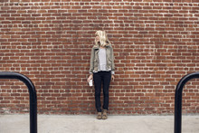 Thoughtful Woman Holding Disposable Glass While Standing Against Brick Wall