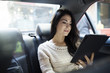 Young woman using tablet computer in taxi