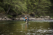 Man Fly Fishing On River Against Trees