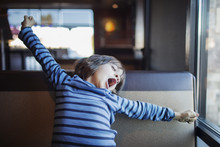 Boy Yawning While Stretching Arms On Sofa At Home