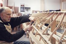 Senior Man Working On Boat In Workshop