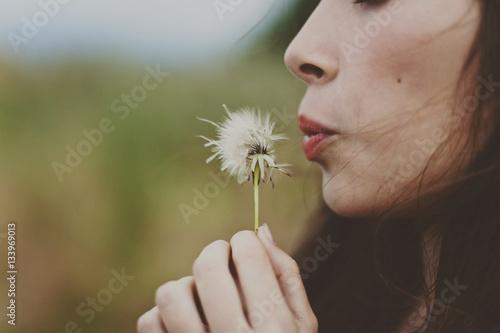 Dandelion Cropped image of girl blowing dandelion on field