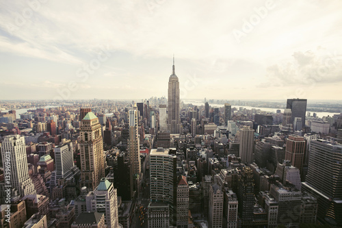 Empire State Building amidst cityscape against sky Poster
