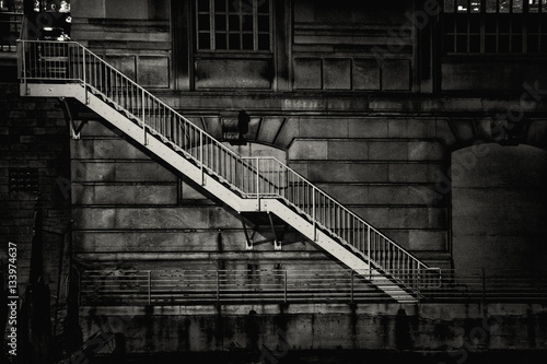 A metal staircase descends from street level down to the Chicago river along the side of a building