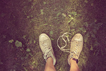 Dirty Sneakers On A Weedy Lawn