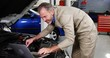 Mechanic using laptop while servicing a car engine
