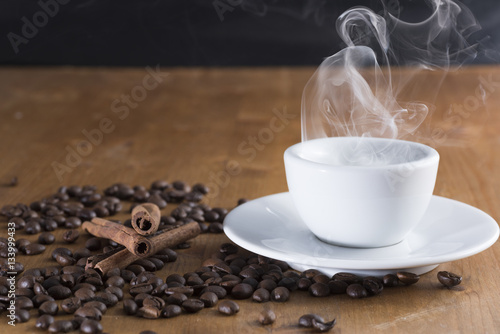 Cadres-photo bureau Café en grains small cup reversed with coffee beans scattered on the wooden table