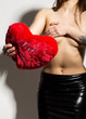 Young beautiful girl with naked body, holding a red heart pillow