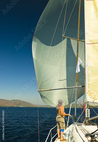 Fotografie, Obraz  Bowman works with spinnaker while racing / Sailor and spinnaker