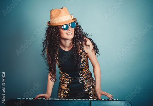 Fototapeta  Rock pop star. Woman playing synthesizer isolated blue background