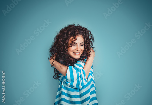 Closeup portrait confident smiling woman holding hugging herself isolated blue wall background Plakat