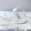 figure in a glass house in the form of two lovers birds. soft focus, bright colors
