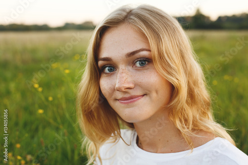 Valokuva A portrait of beautiful young blue-eyed girl with light hair having charming smi