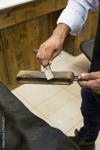 Low section of barber sharpening razor blade on whetstone in shop