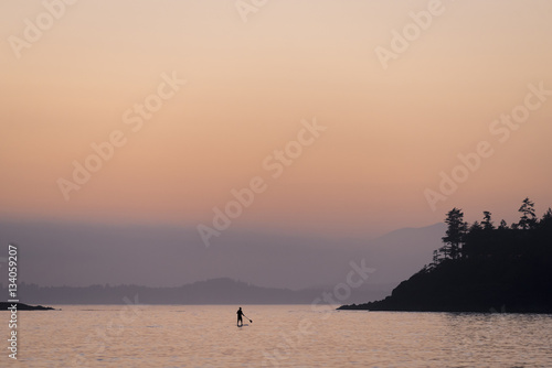 Silhouette person paddleboarding in lake