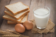Milk Glass With Egg And Bread On Wooden Table
