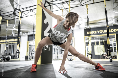Fotografija  Athletic girl does stretching in gym