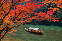 Boatman Punting The Boat For Tourists To Enjoy The Autumn View Along The Bank Of Hozu River In Arashiyama Kyoto, Japan.