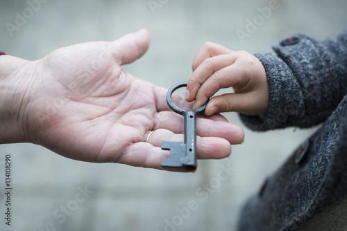 鍵を手渡すお婆さんと孫娘の手 Canvas Print