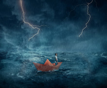 Young Boy In A Orange Paper Boat Sail Lost In The Ocean, In A Stormy Night With Lightnings In The Sky. Adventure And Journey Concept.