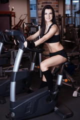 Fototapeta na wymiar Muscular young woman wearing sportswear training on exercise bikes in gym. Intense cardio workout.