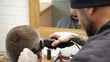 Barber cuts the hair of the client with clipper at barbershop.