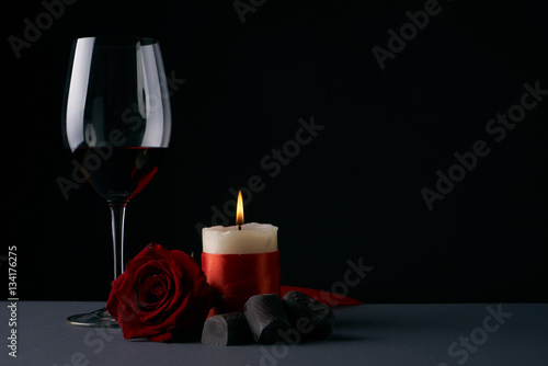 Fotografia  Wineglass with rose, candle and chocolate candies on dark background