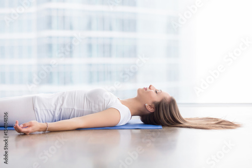 Fotografie, Obraz  Closeup side view of young attractive woman practicing yoga, lying in Savasana e