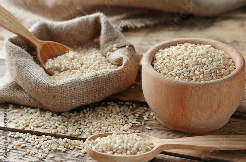 Brown short grain rice on wooden table closeup